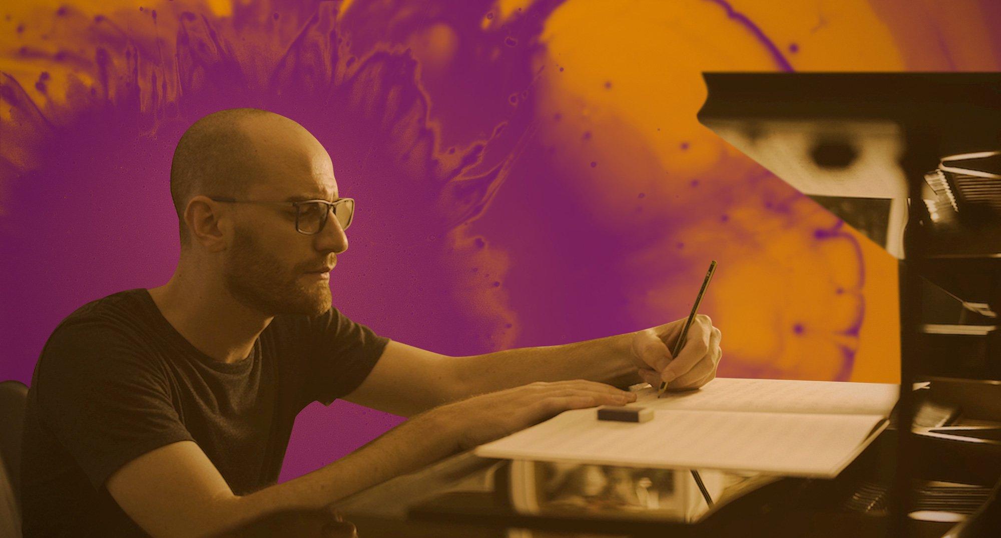 Carmine De Martino, a Soundrop musician, writing at his desk